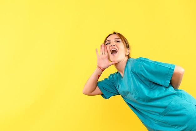 Ärztin der vorderansicht, die gelben raum anruft