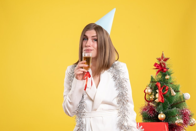 Ärztin der vorderansicht, die glas champagner hält und feiert