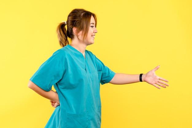 Ärztin der vorderansicht, die handschütteln auf gelbem raum nachahmt