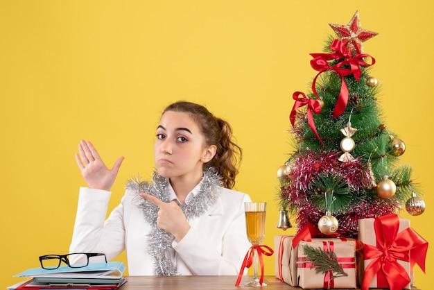 Ärztin der vorderansicht, die hinter ihrem tisch auf gelbem hintergrund mit weihnachtsbaum und geschenkboxen sitzt