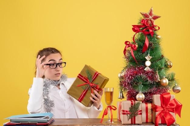 Ärztin der vorderansicht, die hinter ihrem tisch mit weihnachtsgeschenken und baum auf gelbem hintergrund sitzt