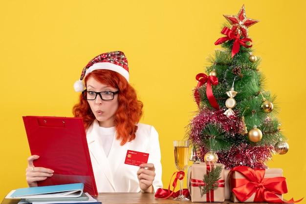 Ärztin der vorderansicht, die hinter ihrem tisch sitzt und bankkarte auf gelbem hintergrund mit weihnachtsbaum und geschenkboxen hält