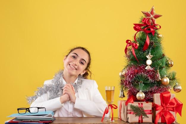 Ärztin der vorderansicht, die hinter tabelle auf gelbem hintergrund mit weihnachtsbaum und geschenkboxen sitzt