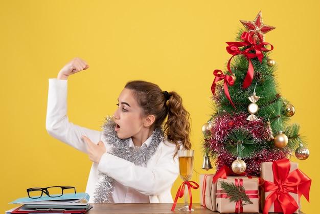 Ärztin der vorderansicht, die hinter tabelle sitzt, die auf gelbem hintergrund mit weihnachtsbaum und geschenkboxen biegt