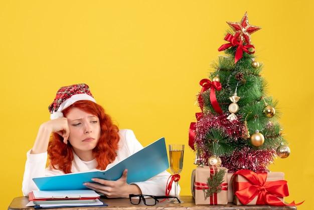 Ärztin der vorderansicht, die hinter tabelle sitzt, die dokumente auf gelbem schreibtisch mit weihnachtsbaum und geschenkboxen liest