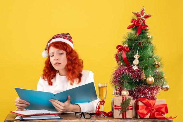 Ärztin der vorderansicht, die hinter tabelle sitzt und dokumente auf gelbem hintergrund mit weihnachtsbaum hält
