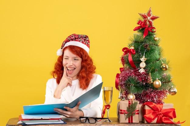 Ärztin der vorderansicht, die hinter tabelle sitzt und dokumente auf gelbem hintergrund mit weihnachtsbaum und geschenkboxen liest