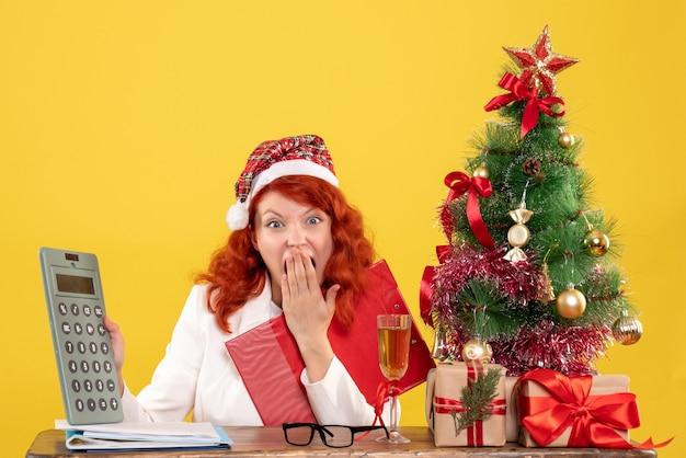 Ärztin der vorderansicht, die hinter tabelle sitzt und rechner auf gelbem hintergrund mit weihnachtsbaum und geschenkboxen hält