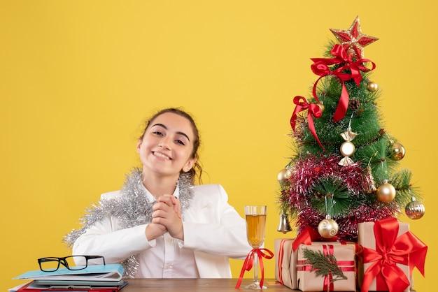 Ärztin der vorderansicht, die hinter tisch lächelnd auf gelbem hintergrund mit weihnachtsbaum und geschenkboxen sitzt