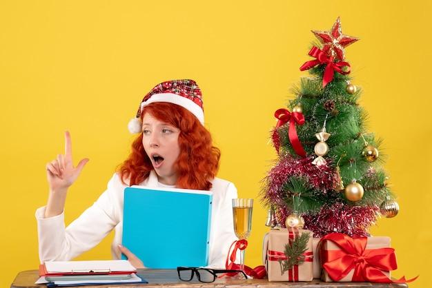 Ärztin der vorderansicht, die hinter tisch mit dokumenten in ihren händen auf gelbem hintergrund mit weihnachtsbaum und geschenkboxen sitzt