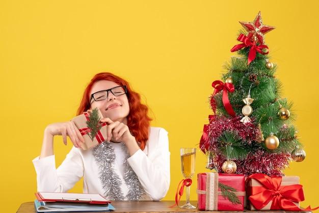 Ärztin der vorderansicht, die hinter tisch mit weihnachtsgeschenken auf gelbem hintergrund mit weihnachtsbaum und geschenkboxen sitzt