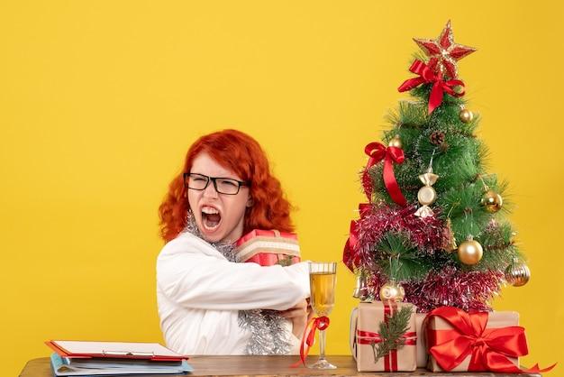 Ärztin der vorderansicht, die hinter tisch mit weihnachtsgeschenken auf gelbem hintergrund sitzt