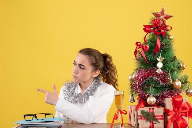 Ärztin der vorderansicht, die hinter tisch mit weihnachtsgeschenken und baum auf gelbem hintergrund sitzt