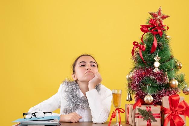 Ärztin der vorderansicht, die hinter tisch mit weihnachtsgeschenken und baum sitzt, der sich auf gelbem hintergrund gelangweilt fühlt