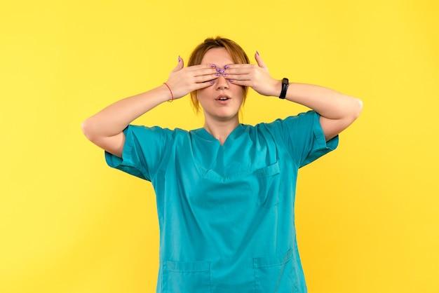 Ärztin der vorderansicht, die ihre augen auf gelbem raum bedeckt