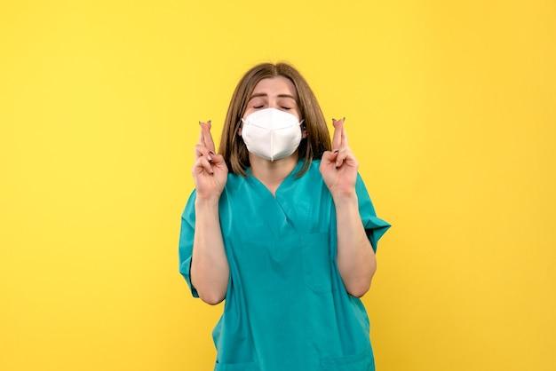 Ärztin der vorderansicht, die ihre finger auf gelbem raum kreuzt