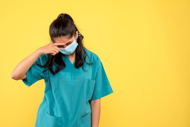 Ärztin der vorderansicht, die ihren kopf stehend biegt