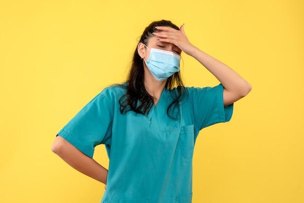 Ärztin der vorderansicht, die ihren rücken und kopf stehend hält