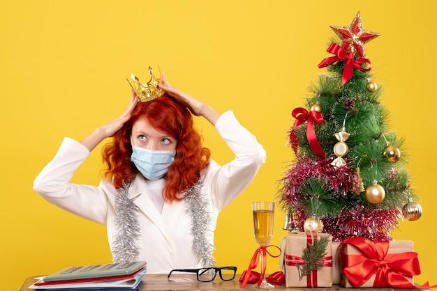 Ärztin der vorderansicht, die in der maske mit weihnachten sitzt, präsentiert das tragen der krone auf gelbem hintergrund