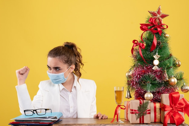 Ärztin der vorderansicht, die in der sterilen maske auf gelbem hintergrund mit weihnachtsbaum und geschenkboxen sitzt