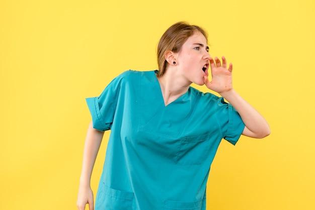 Ärztin der vorderansicht, die jemanden auf gelbem hintergrundmediziner-emotionskrankenhausgesundheit ruft