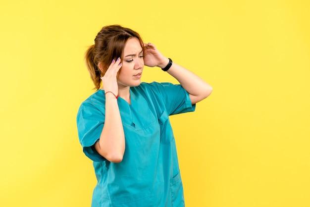 Ärztin der vorderansicht, die kopfschmerzen auf gelbem raum hat