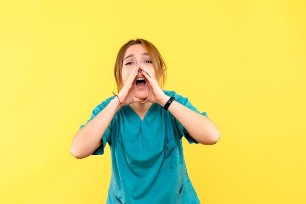 Ärztin der vorderansicht, die laut gelben raum anruft