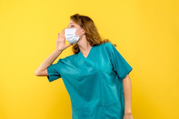 Ärztin der vorderansicht, die maske auf gelbem raum anruft