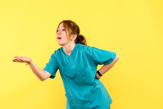 Ärztin der vorderansicht, die mit jemandem auf gelbem raum argumentiert