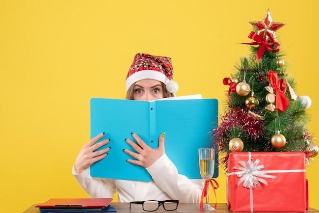 Ärztin der vorderansicht, die mit weihnachten sitzt, präsentiert das halten von dateien auf gelbem hintergrund