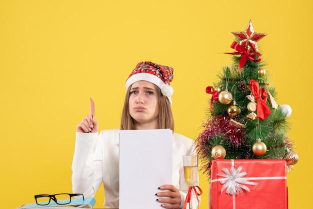 Ärztin der vorderansicht, die mit weihnachten sitzt, präsentiert das halten von dokumenten auf gelbem schreibtisch