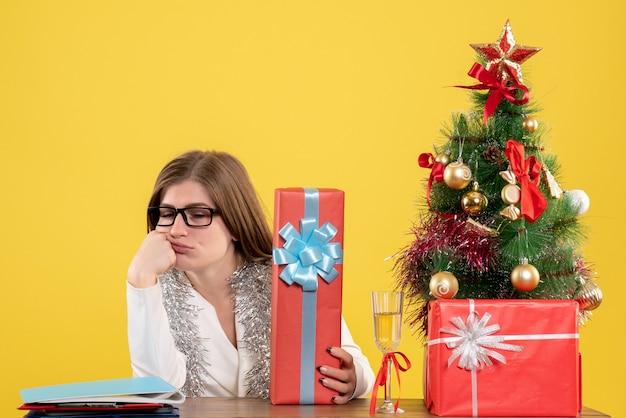 Ärztin der vorderansicht, die mit weihnachtsgeschenken und baum auf gelbem hintergrund sitzt