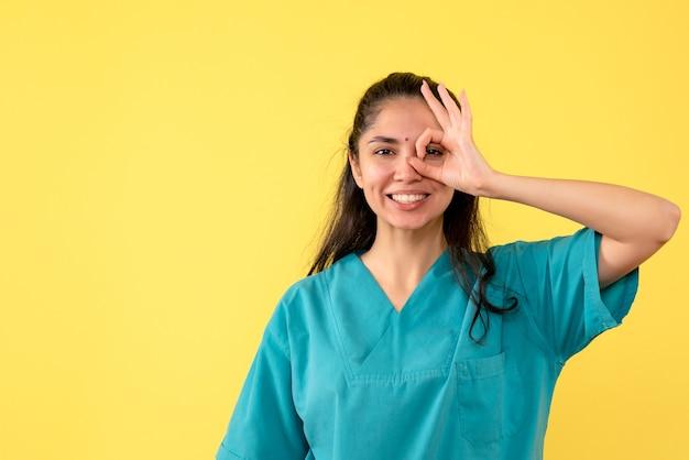 Ärztin der vorderansicht, die okey zeichen vor ihr stehendes auge setzt