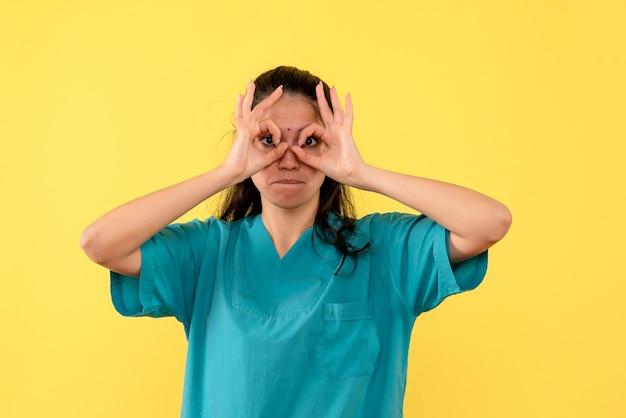 Ärztin der vorderansicht, die okey zeichen vor ihre stehenden augen setzt