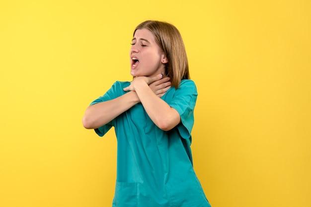 Ärztin der vorderansicht, die sich auf gelbem raum erstickt