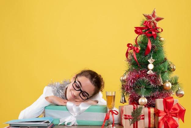Ärztin der vorderansicht, die um weihnachtsgeschenke und baum auf gelbem hintergrund sitzt