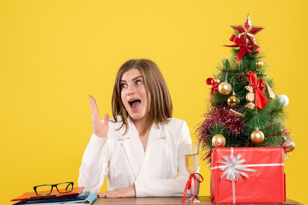 Ärztin der vorderansicht, die vor ihrem tisch auf gelbem hintergrund mit weihnachtsbaum und geschenkboxen sitzt