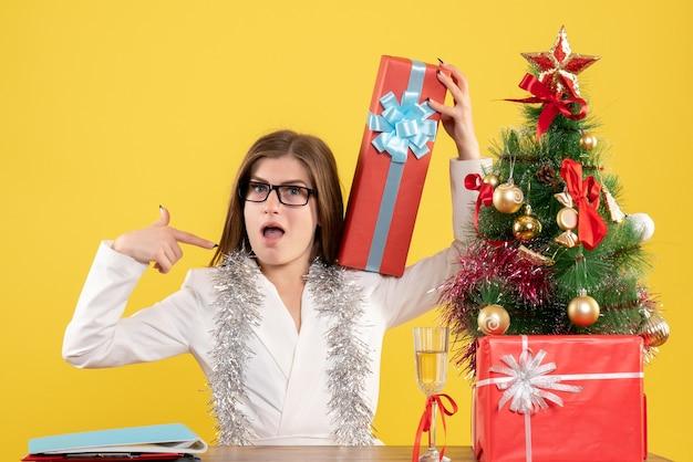 Ärztin der vorderansicht, die vor tisch mit geschenken und baum auf gelbem hintergrund mit weihnachtsbaum und geschenkboxen sitzt