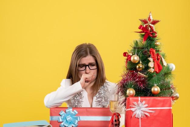 Ärztin der vorderansicht, die vor tisch mit geschenken und baum auf gelbem schreibtisch sitzt