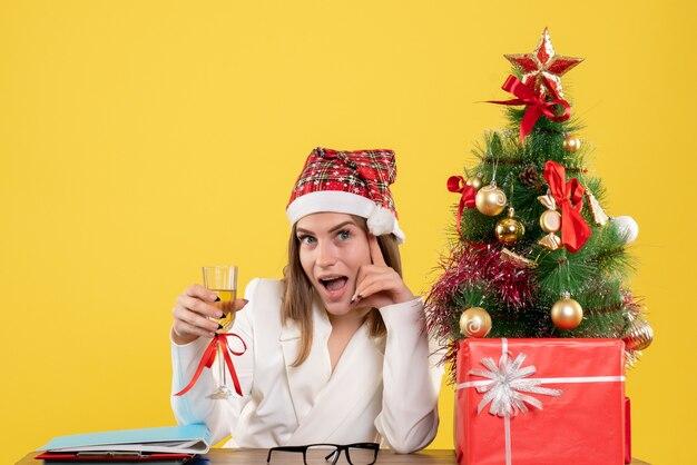 Ärztin der vorderansicht, die weihnachten mit champagner feiert