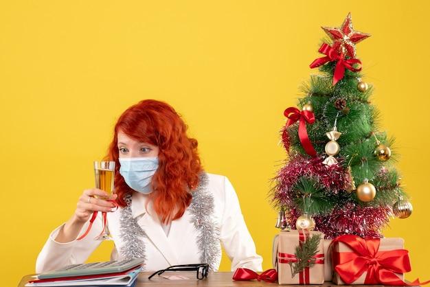 Ärztin der vorderansicht, die weihnachten mit glas champagner feiert