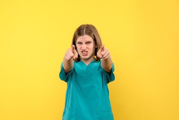 Ärztin der vorderansicht, die wütend auf gelben raum zeigt
