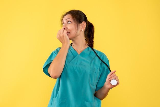 Ärztin der vorderansicht im medizinischen hemd, das auf gelbem hintergrund nervös fühlt
