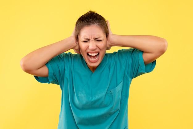 Ärztin der vorderansicht im medizinischen hemd, das ihre ohren auf gelbem hintergrund schließt