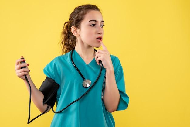 Ärztin der vorderansicht im medizinischen hemd, die ihren druck prüft, virusgesundheitsgefühls-covid-19-pandemie