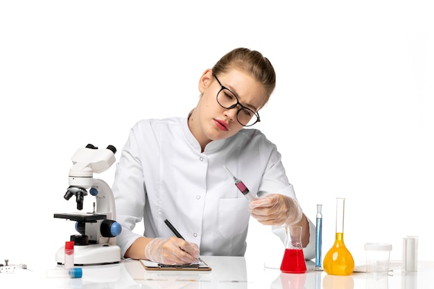 Ärztin der vorderansicht im weißen medizinischen anzug, der injektion auf hellweißem schreibtisch hält
