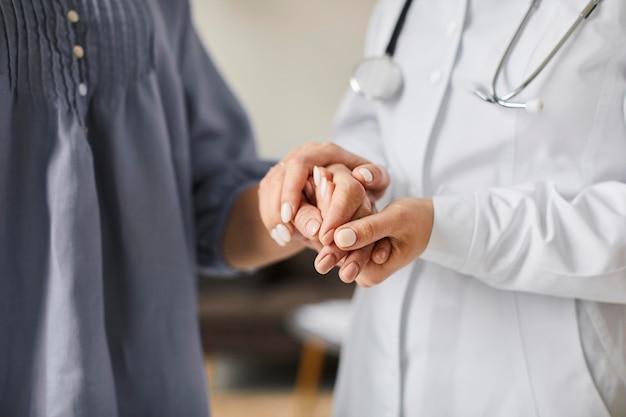 Ärztin des covid recovery centers, die die hände älterer patienten hält