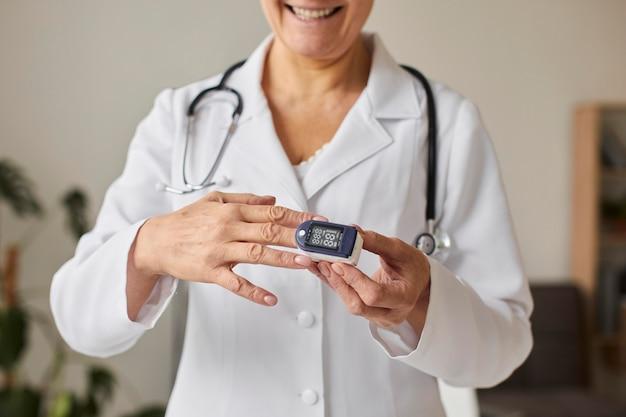 Ärztin des smiley elder covid recovery centers unter verwendung eines oximeters