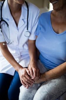 Ärztin, die ältere frau im schlafzimmer tröstet