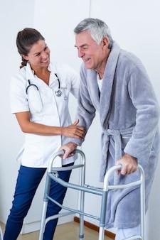 Ärztin, die älterem mann hilft, mit wanderer zu gehen
